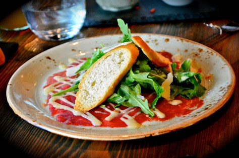 Beef Carpaccio - thin slices of beef topped with fresh rocket, olive crostini & a mustard dressing
