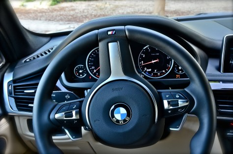 M Leather steering wheel with multifunction buttons and gearshift paddles