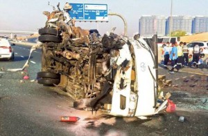 Image Credit: Courtesy: Dubai Police The wreckage of an overturned bus after the accident on Emirates Road on Saturday. The bus collided with a truck, killing 13 people and injuring 15.