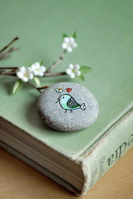 Little bird painting on a gray rock.