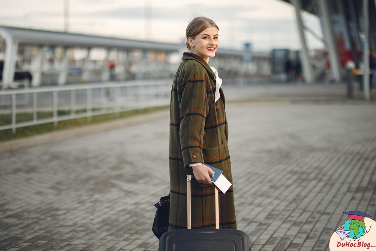 smiling female traveler walking with suitcase and passport near train station