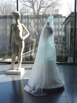 "Johannes Brus' ""Kontrolleurin"" links, das ""Gespenst"" rechts in der Glashalle des Lehmbruck Museums. Foto: Petra Grünendahl."