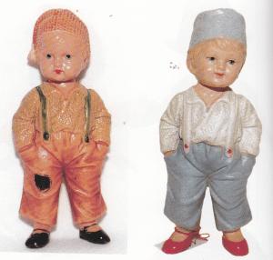 """De to 16 cm høje dukker her er fra 20erne og begge mærket med """"pigemærket og Germany"""". Drengene tv hedder """"Michel"""", drengefigur med Igodi-hovedpatent (se artiklen om Hunaeus-dukkerne) Ikke-bevægelige arme og ben. Huen og tøjet er modelleret og påmalet. Dukken th kaldes blot """"Dreng med hue"""", og kan beskrives som Michel tv.— Der blev fremstillet flere udgaver af disse dukker med samme krop, men med forskellige hoveder."""