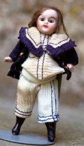 lille dukkehus dreng af den lille slanke type, som der blev lavet så mange af med sorte støvler, hovedet sidder fast med store brune øjne og lukket mund. Han er i sit originale tøj - jeg måtte lave et manglende bukseben, men det er fint tidligt matrostøj, han har også en sølvhjelm, kun 7cm høj