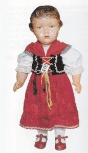 Pigen her er fra 1936, 56 cm høj og mærket SNF i vandret rude, dvs. fra Nobel. Stådukke med bevægelige led, drejeligt hoved, ansigtet har et stærkt melankolsk udtryk. Lukkeøjne af glas, lukket mund, kraftigt præget hår. Folkedragten er original.