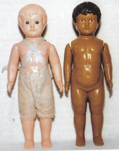 """Yderst tv et par """"tvillinger"""", dvs. stådukker med forskellig hudfarve. Den hvide dukke er umærket. Den mørke med W i cirkel. De er fremstillet af gennemfarvet celluloid, har fast hoved og bevægelige arme. Den mørke dukke har påmalede øjne og hår, den lyse indsatte glasøjne, begge har åben/lukket mund De er fra ca. 1900-1910 og 25 cm høje!"""
