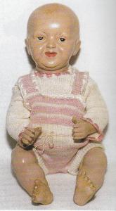 Dukkedrengen her er 31 cm høj og har drejeligt hoved, bevægelige arme og ben. Dukken dateres til ca. 1914 - og må efter ansigtsudtrykket betegnes som en karakterdukke. Øjnene er malede og den let smilende mund er åben/lukket. Håret er påmalet. På hovedet er dukken mærket med Stork A 6, og på kroppen med storkelogoet.