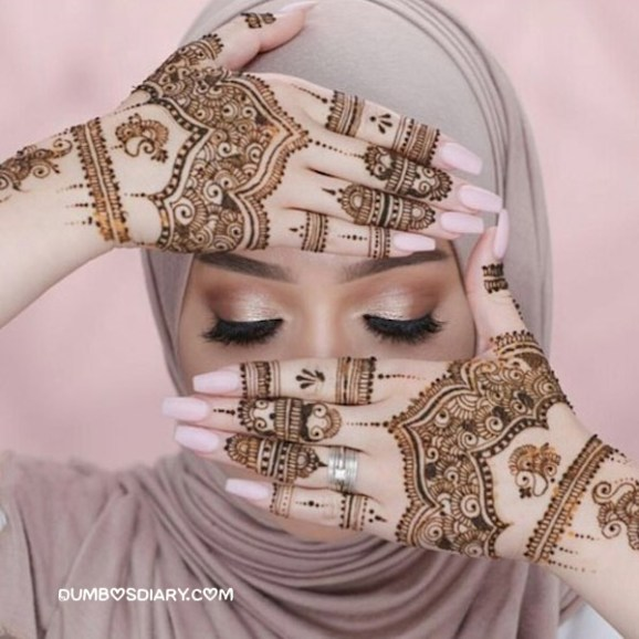 Cute hijabi girl hidding her face with henna hands