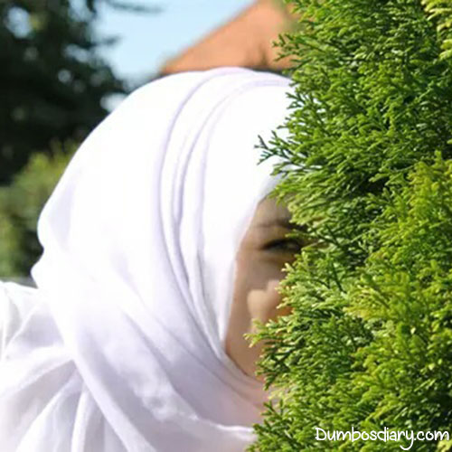 Hijabi girl hiding behind bush