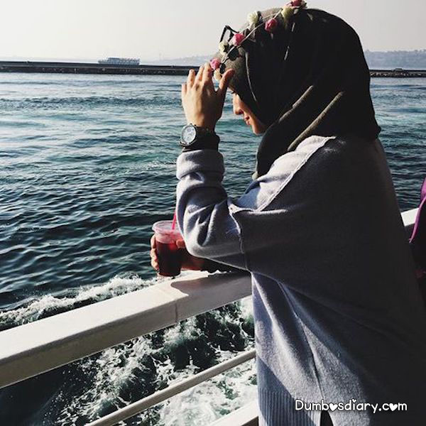 Hijabi Girl Standing On Beach With Drink