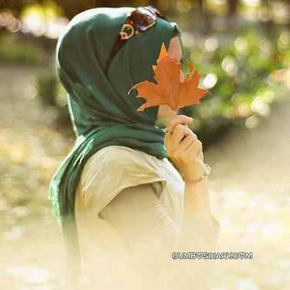 Pretty girl hidding her face with maple leave