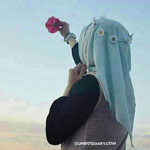 Pretty hijabi girl hidden face holding flower in air