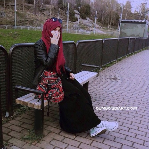 Pretty hijabi girl in black gown hidding her face