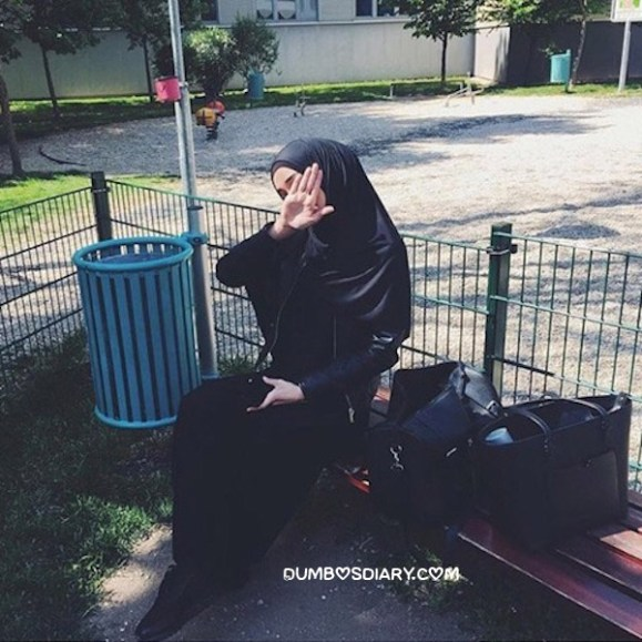 Pretty muslim girl sitting on bench in park or garden