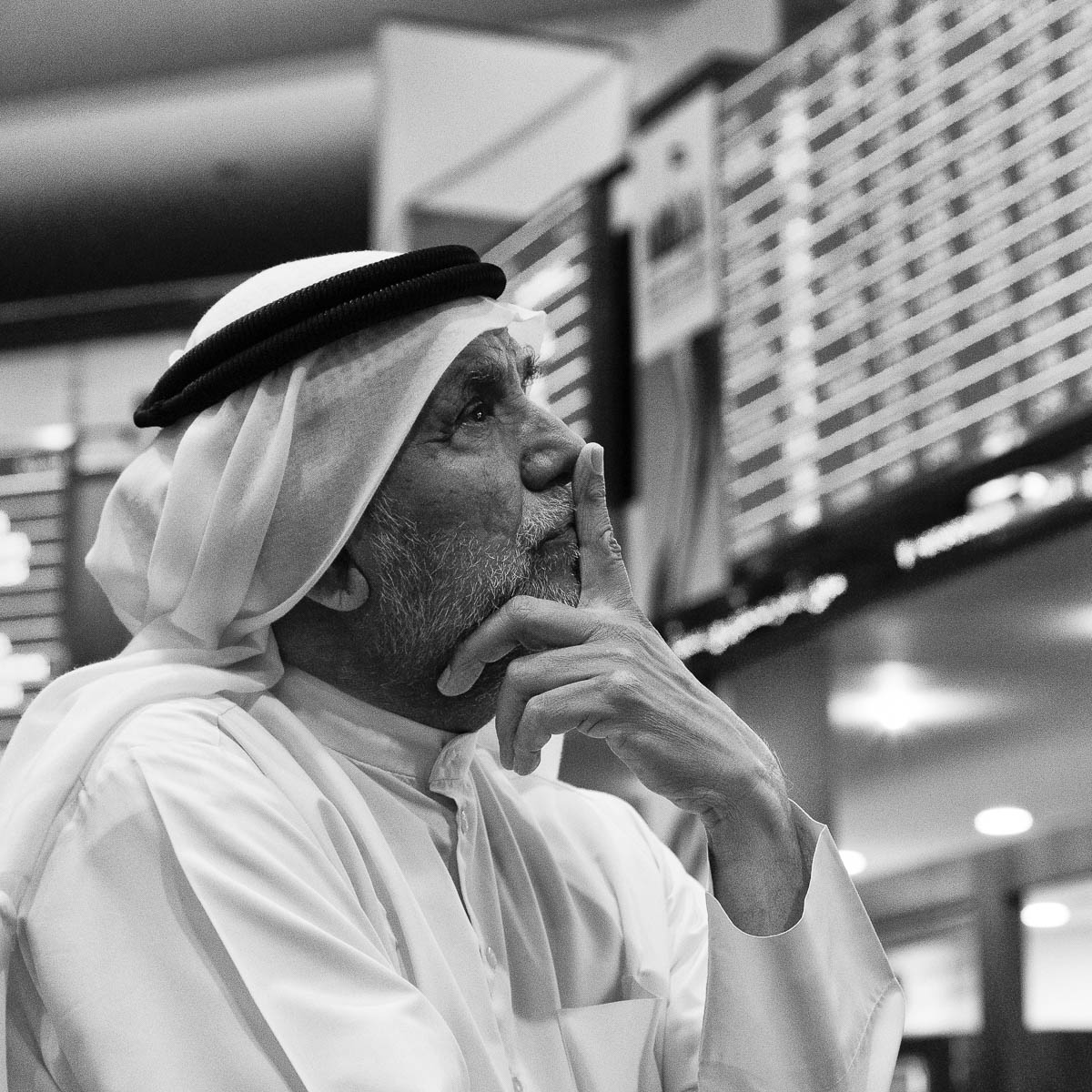 A local trader watches the prices of stocks during a time of market instability at the Dubai Stock Exchange