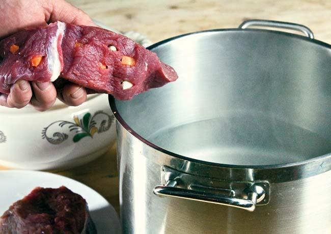 закладка нашпигованного мяса в кастрюлю с кипящей водой