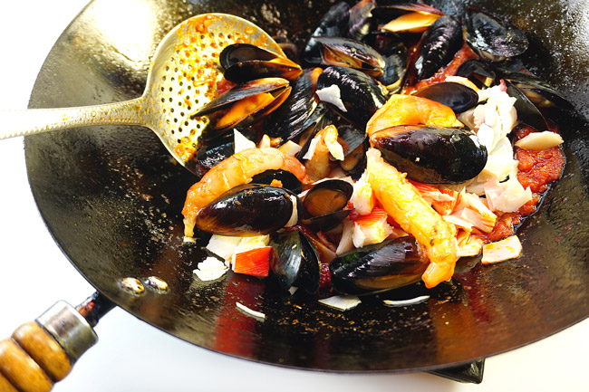 добавление морепродуктов для соуса к спагетти с морепродуктами