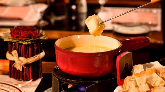 Red pot pot with cheese fondu and bread crumbs in basket with table decoration