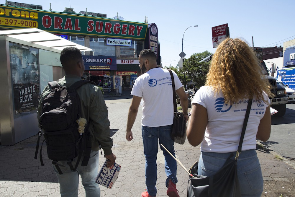 "Canvassers from Dominicanos USA walk down the street in Corona, Queens. ""We get to meet a lot of people and develop those bonds with the community,"" says Yohan Diaz, left."
