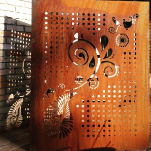 A Cor-ten steel custom pattern privacy screen using hexagons and paisley installed in downtown Toronto.