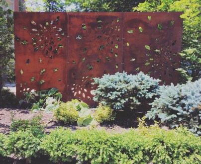 This seed cut out in Toronto, Ontario sits beside a driveway and adds a dramatic art piece to a front yard. Corten steel screen.