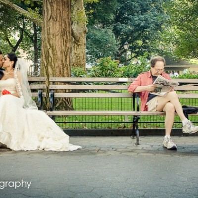 An Indian wedding couple spontaneously kisses on a park bench in New York City sitting next to a man reading a newspaper in Madison Square Park.