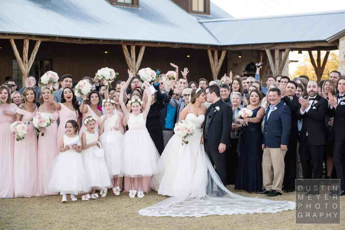 A fun wedding group photo with people laughing and looking on as the groom kisses his bride on their wedding day.