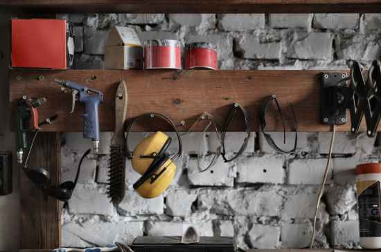 various instruments hanging on wooden board in garage
