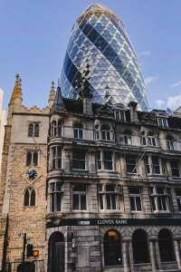 old buildings in the City of London with the modern skyscraper Gherkin behind it
