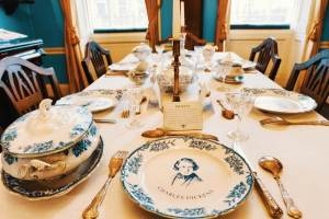 close-up of the dining table in Charles Dickens's London home set with cutlery and plates with one saying the name Charles Dickens and having his portrait printed on it