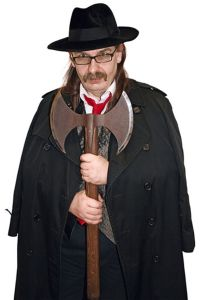 Kim Newman posing with a battle axe in his hands wearing a hat and long coat
