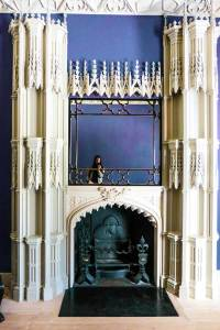 fireplace with two white Gothic tower decorations at either side and Zarina taking a selfie of herself in the mirror over the fireplace