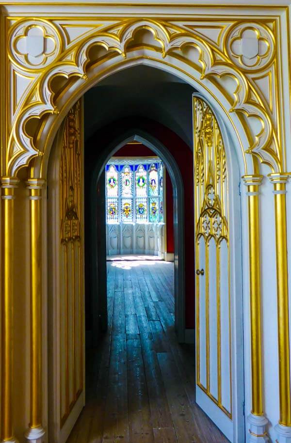 looking into the Round Room in the near distance through a set of heavily decorated doors with gold-painted accents