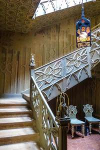 Staircase at Strawberry Hill House with a lantern, white wooden balustrade with carvings and sculptures of antelopes in golden cages