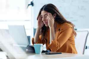 Business young woman with headache working with laptop in the office.