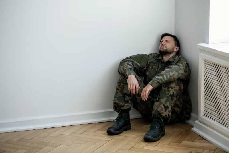 Depressed army man in uniform sitting in a corner of an empty ro
