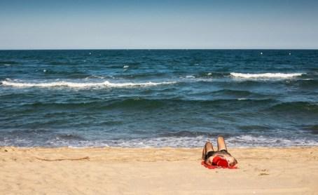 """Canet en Roussillon, 28 mai 2020, Les plages rÈcemment rouvertes sont dÈsormais """"dynamique"""", ainsi le farniente et le bronzage stationnaire, sur serviette sont interdit. Entre respect des rËgles et pratiques sportives ou non respect et bain de soleil sous un parasol, la pratique de la plage en mai 2020 s'en retrouve inhabituellement modifiÈ. Homme allongÈ sur sa serviette, face ‡ la plage."""