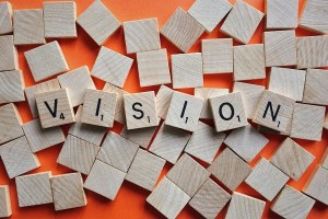 """the word """"vision"""" spelled out of Scrabble tiles, with other tiles, face down, strewn about"""