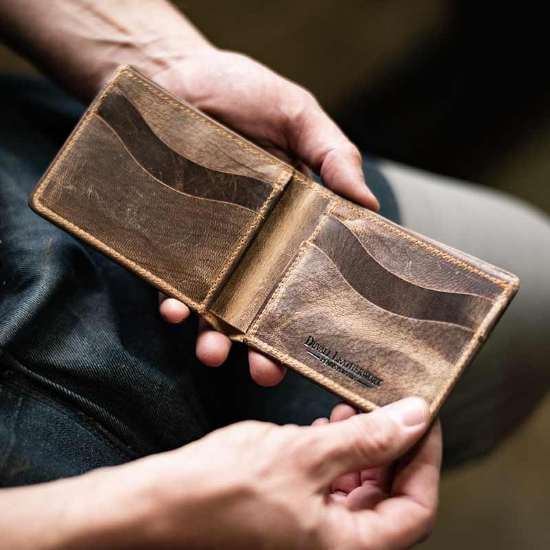 Leather craftsman inspecting a leather wallet