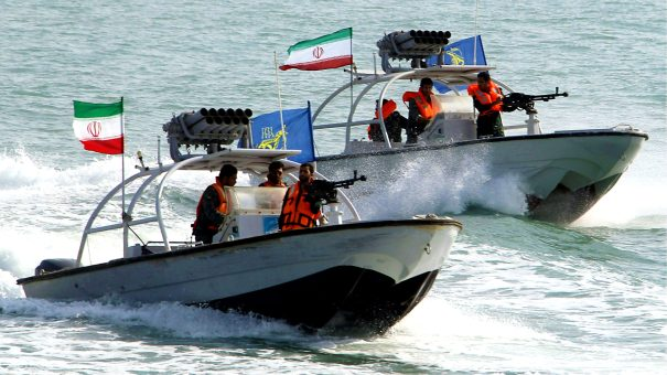 """(COMBO) This combination of file pictures created on July 22, 2019 shows Iranian Revolutionary Guards driving speedboats at the port of Bandar Abbas on July 02, 2012 (L), and the amphibious assault ship USS Boxer (LHD 4) as transiting the East Sea during exercises on March 7, 2016. - Iran's seizure of a British-flagged oil tanker in the Strait of Hormuz was a """"legal measure"""", the spokesman for the Islamic republic's government said on July 22. Iran impounded the Stena Impero tanker on allegations it failed to respond to distress calls and turned off its transponder after hitting a fishing boat. (Photos by Atta KENARE and Craig Z. Rodarte / various sources / AFP) / RESTRICTED TO EDITORIAL USE - MANDATORY CREDIT """"AFP PHOTO /US NAVY/GREG Z RODARTE"""" - NO MARKETING NO ADVERTISING CAMPAIGNS - DISTRIBUTED AS A SERVICE TO CLIENTS"""