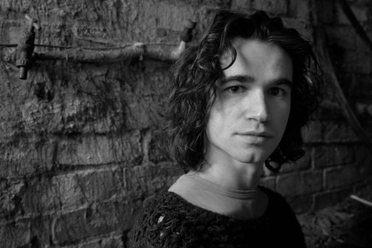 Ollie Smith portrait B&W black and white man long hair wall bricks