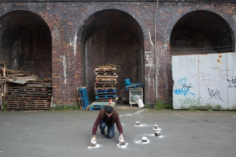 wide angle shot of performance artist Matt Smith positioning bricks covered in flour