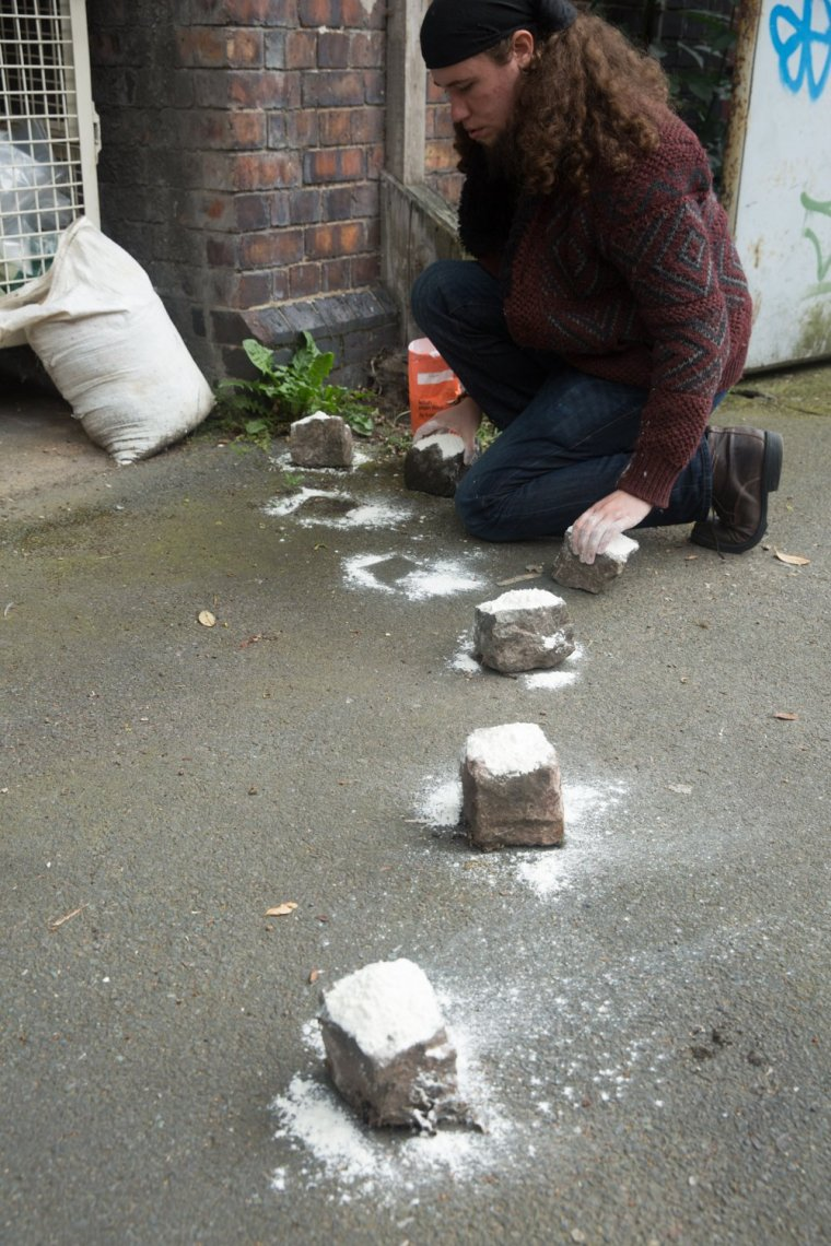 performance artist Matt Smith positioning bricks covered in flour in Leicester