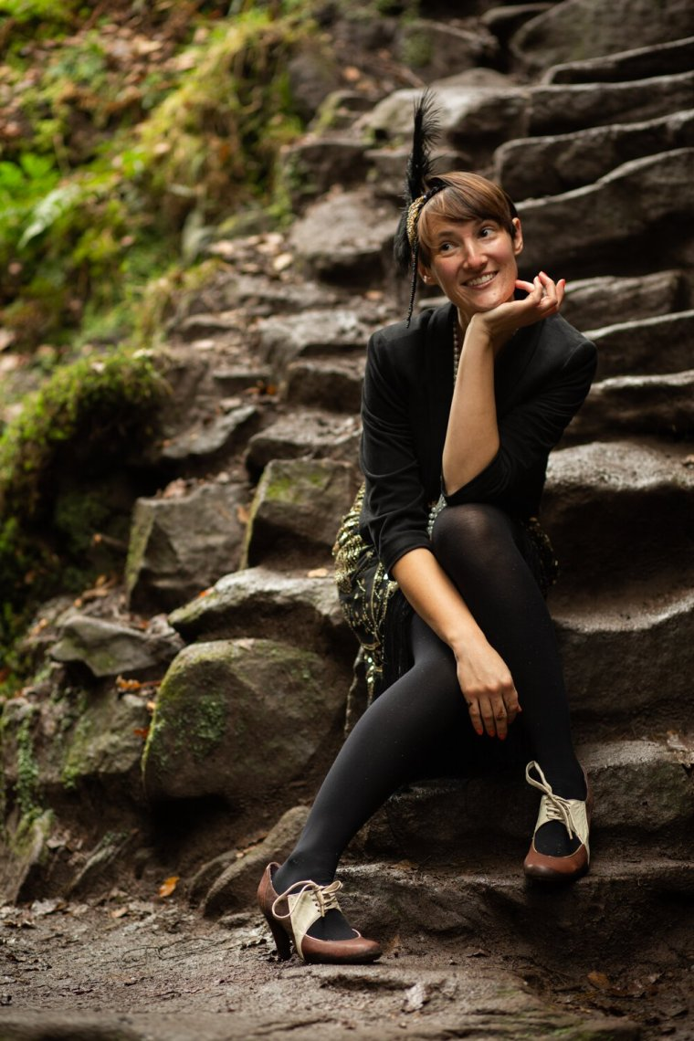 IsoElegant wearing a flapper dress, sitting smiling on rock steps in Lud's Church.
