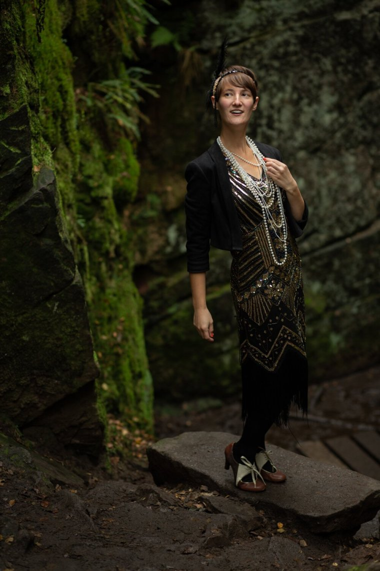 IsoElegant smiling, standing wearing a flapper dress, amongst dark green rocks.