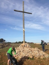Caroline placing a rock in front of the cross as a prayer. Pilgrims bring rocks from their homelands as prayers to this cross.