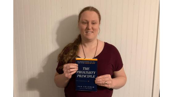 "Katie Corbett holds the book ""The Proximity Principle"""