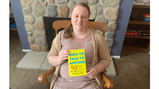 """Katie Corbett holds the book """"How to Talk to Anyone"""""""