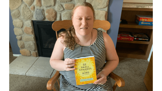 """Katie Corbett holds the book """"52 Small Changes"""""""
