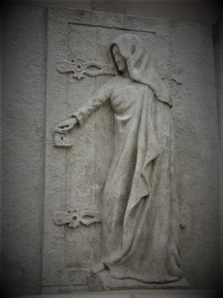 Woman opening a door to a Family tomb at Sümeg Cemetery Hungary